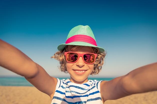 Szczęśliwe dziecko na wakacjach dziecko bawiące się na plaży aktywny zdrowy styl życia