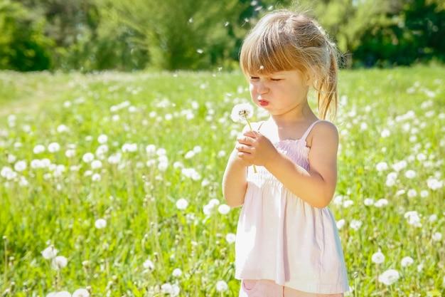 Szczęśliwe dziecko na zewnątrz dmuchanie mniszka lekarskiego w parku