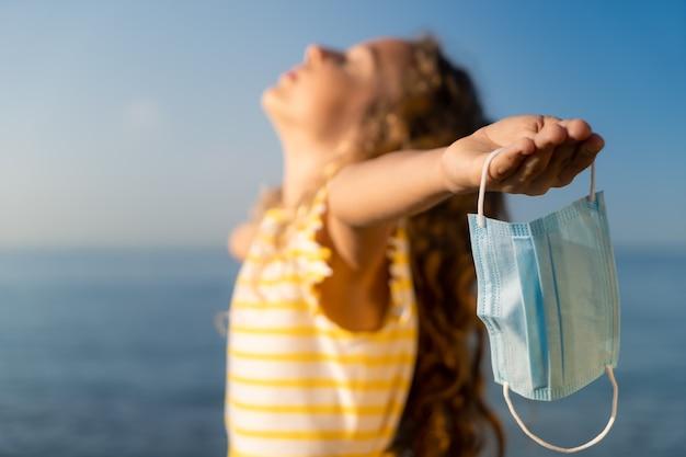 Szczęśliwe dziecko nosi maskę medyczną na zewnątrz na tle błękitnego nieba