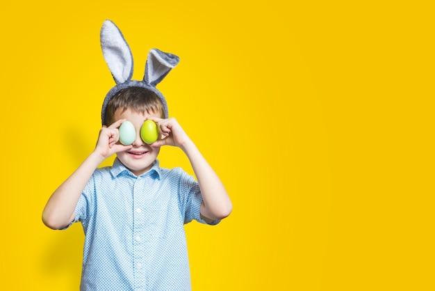 Szczęśliwe dziecko nosi uszy królika i trzyma kolorowe pisanki przed oczami na żółtym tle