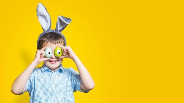 Szczęśliwe dziecko nosi uszy królika i trzyma kolorowe pisanki