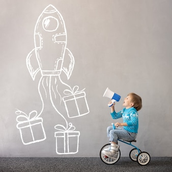 Szczęśliwe dziecko noszące kostium świąteczny dziecko jeżdżące na rowerze święta bożego narodzenia koncepcja wakacje