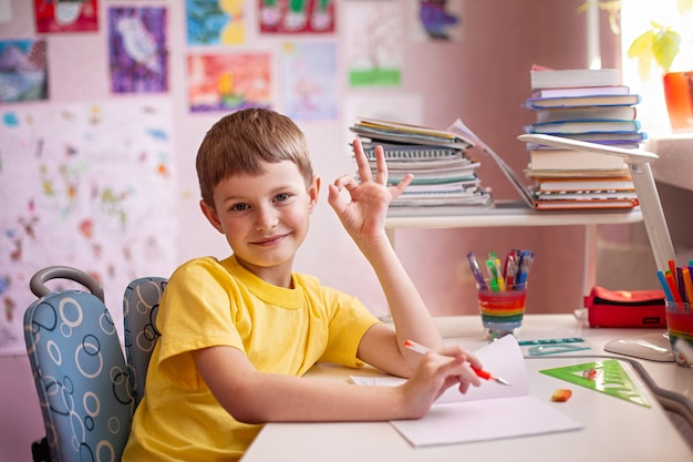 Szczęśliwe dziecko odrabiania lekcji. uczenie się w domu. kształcenie na odległość w domu.