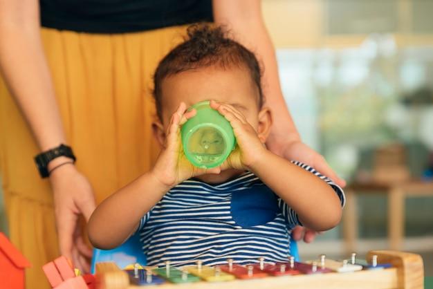 Szczęśliwe dziecko pije wodę i bawi się klockami w przedszkolu.