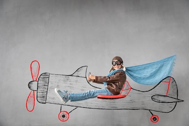 Szczęśliwe dziecko pilot podróżuje wyimaginowanym samolotem
