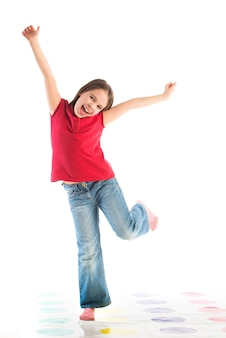 Szczęśliwe dziecko pozowanie w ubrania dla dzieci, stojąc na jednej nodze, z podniesionymi rękami