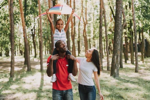 Szczęśliwe dziecko prowadzi latający latawiec w lesie.