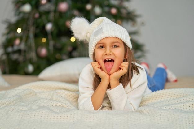 Szczęśliwe dziecko przebywa na łóżku w pobliżu choinki