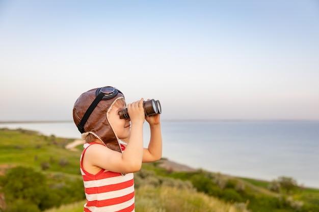 Szczęśliwe dziecko przeciw błękitnemu morzu i niebu. śmieszne dziecko na wakacjach. koncepcja podróży i przygód