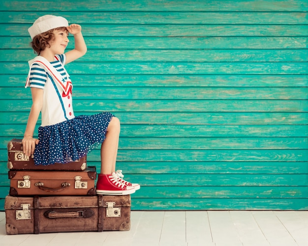 Szczęśliwe dziecko siedzące na starej walizce ubrane jak marynarz patrzący w przyszłość na niebieskim drewnianym tle