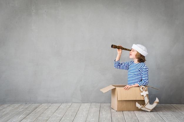 Szczęśliwe dziecko siedzące w kartonowym pudle ubrane jak marynarz z lunetą na szarym tle
