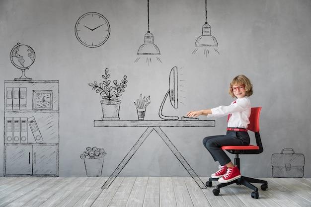 Szczęśliwe dziecko siedzi przy biurku w wyimaginowanym biurze