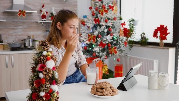 Szczęśliwe dziecko siedzi przy stole w udekorowanej kuchni, oglądając boże narodzenie wideo online na komputerze typu tablet