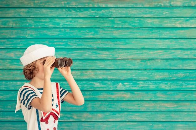 Szczęśliwe dziecko siedzi trzymając lunetę ubrane jak marynarz na niebieskim drewnianym tle