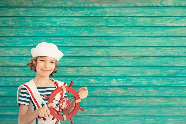 Szczęśliwe dziecko siedzi trzymając ster w stroju marynarza na niebieskim drewnianym tle