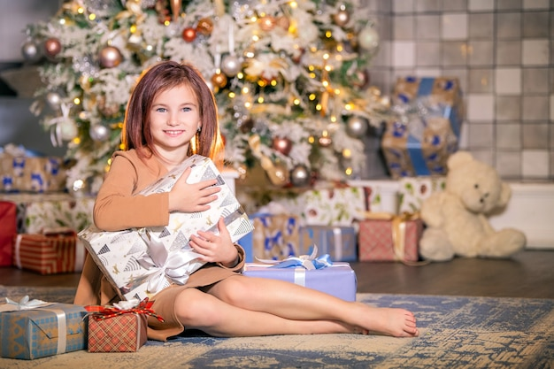 Szczęśliwe dziecko siedzi w pobliżu choinki z dużym pudełkiem z prezentem w rękach