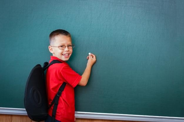 Szczęśliwe dziecko stojące przy tablicy ze szkolnym plecakiem w okularach