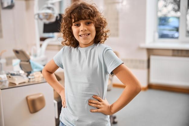 Szczęśliwe dziecko szeroko się uśmiecha, stojąc w gabinecie dentystycznym i patrząc w kamerę