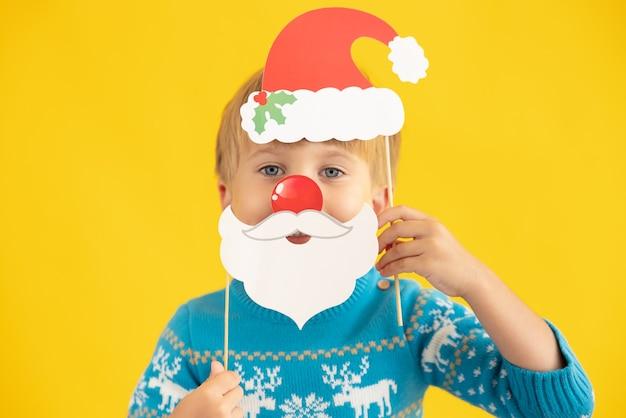 Szczęśliwe dziecko trzyma czapkę i brodę świętego mikołaja na żółtym tle koncepcja świątecznych wakacji