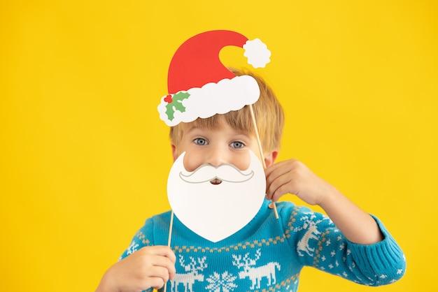 Szczęśliwe dziecko trzyma czapkę świętego mikołaja i brodę