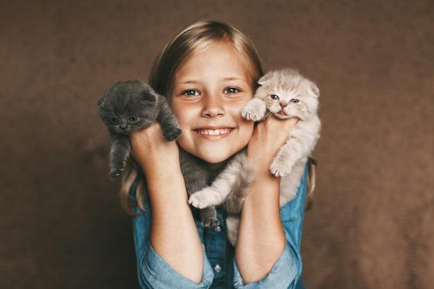 Szczęśliwe dziecko trzyma piękne brytyjskie kocięta