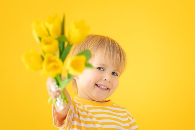 Szczęśliwe dziecko trzymając wiosenny bukiet tulipanów na żółtej ścianie.