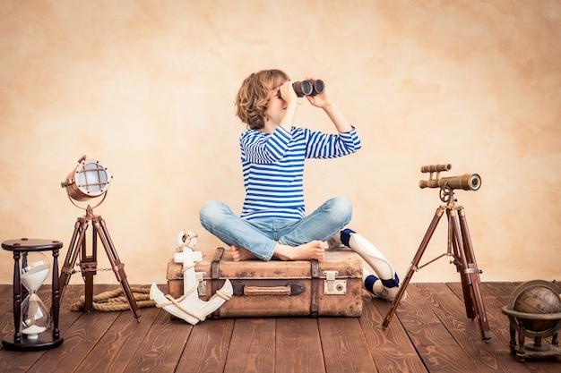 Szczęśliwe dziecko trzymające lornetkę siedzące na zabytkowej walizce na tle motywu marynarza