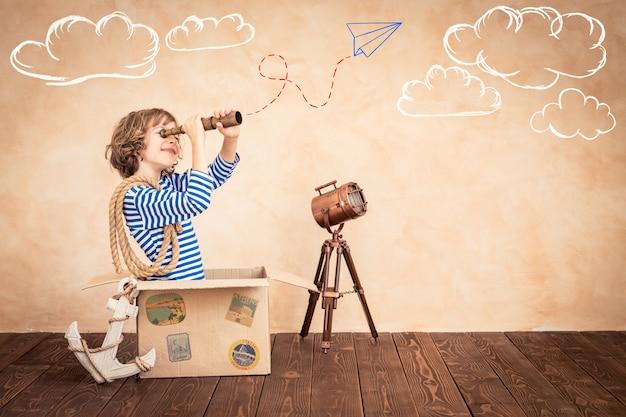 Szczęśliwe dziecko trzymające lunetę siedzące na vintage walizce z bajkami na tle motywu marynarza
