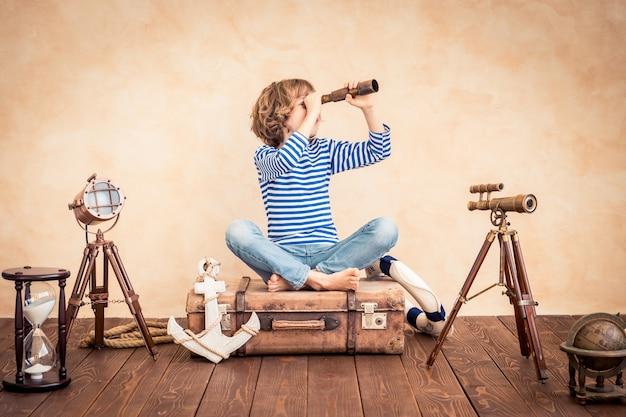 Szczęśliwe dziecko trzymające lunetę siedzące na zabytkowej walizce na tle motywu marynarskiego