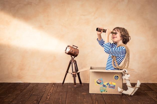 Szczęśliwe dziecko trzymające lunetę siedzące na zabytkowej walizce z naciskiem na tło tematu marynarskiego