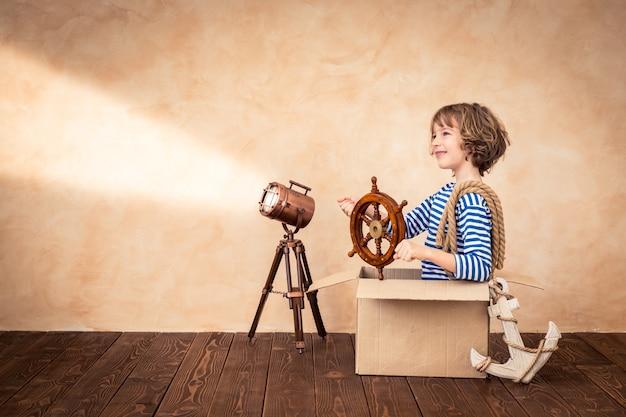 Szczęśliwe dziecko trzymające ster siedzące na zabytkowej walizce z naciskiem na tło tematu marynarskiego