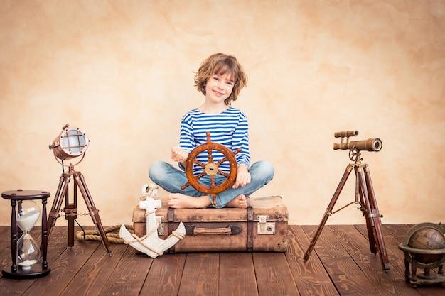 Szczęśliwe dziecko trzymające ster siedzi na zabytkowej walizce na tle motywu marynarza