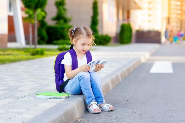 Szczęśliwe dziecko, uczennica z plecakiem i rachunkami w rękach, siada na krawężniku w szkole i uczy się liczyć liczby, koncepcja wraca do szkoły