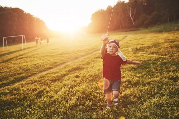 Szczęśliwe dziecko uruchamia latawiec w polu o zachodzie słońca. mały chłopiec i dziewczynka na wakacjach