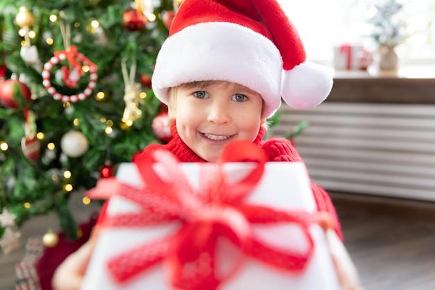 Szczęśliwe dziecko w czapce świętego mikołaja dziecko trzyma pudełko na prezent