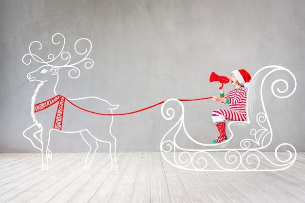 Szczęśliwe dziecko w czasie świąt bożego narodzenia. zabawne dziecko bawiące się w domu