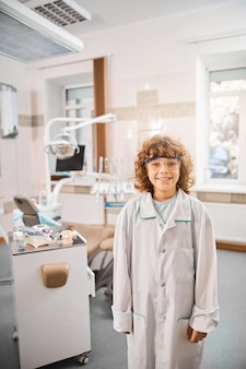 Szczęśliwe dziecko w fartuchu i okularach ochronnych stojąc w klinice dentystycznej
