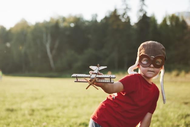 Szczęśliwe dziecko w hełmie pilota bawi się drewnianym samolocikiem i marzy o zostaniu latającym