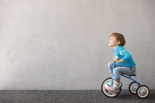 Szczęśliwe dziecko w kostiumie świątecznym dziecko jeżdżące na rowerze!