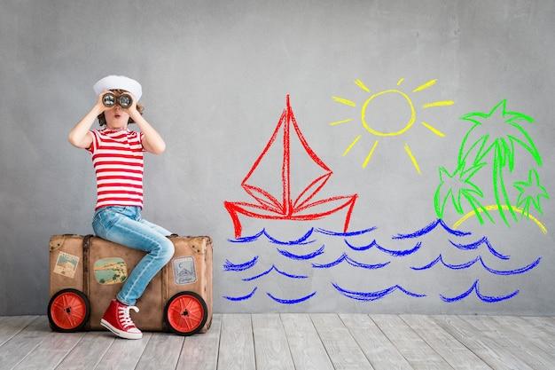 Szczęśliwe dziecko w marynarskim stroju bawiące się w pomieszczeniu z lunetą na szarym tle z rysunkami