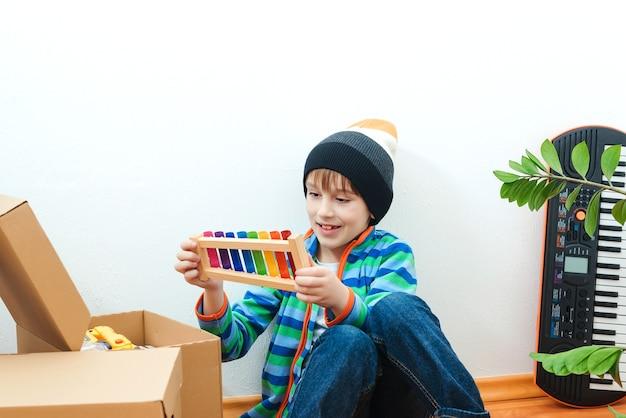 Szczęśliwe dziecko w nowym domu. zakwaterowanie młodej rodziny z dzieckiem. rodzina wprowadza się do nowego mieszkania. chłopiec bawiący się w ich nowym mieszkaniu. słodkie dziecko pomaga rozpakowywać pudełka.