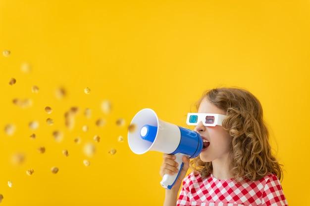 Szczęśliwe dziecko w okularach 3d i krzycząc przez megafon przed żółtą ścianą.