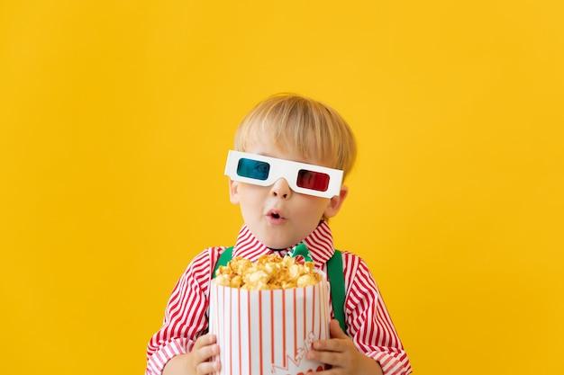 Szczęśliwe dziecko w okularach 3d i trzymając popcorns przed żółtą ścianą.