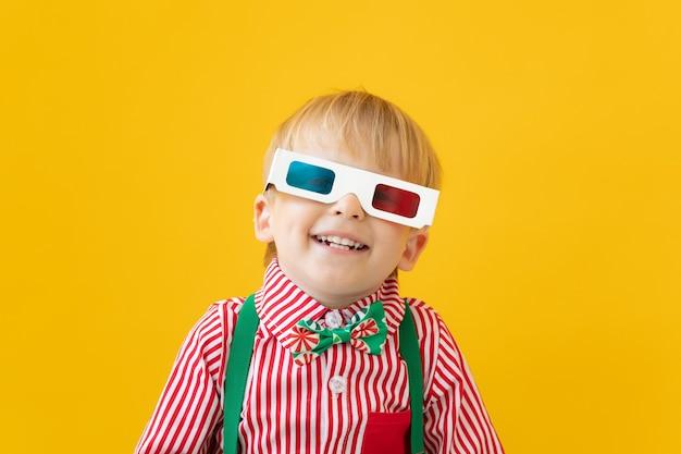 Szczęśliwe dziecko w okularach 3d. zdziwiony dzieciak przed żółtą ścianą. koncepcja czasu kina i filmu