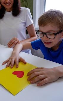 Szczęśliwe dziecko w okularach własnoręcznie zrobiło kartkę na walentynki na dzień ojca
