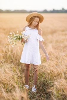Szczęśliwe dziecko w polu pszenicy. piękna dziewczyna w białej sukni w słomkowym kapeluszu z dojrzałej pszenicy w rękach