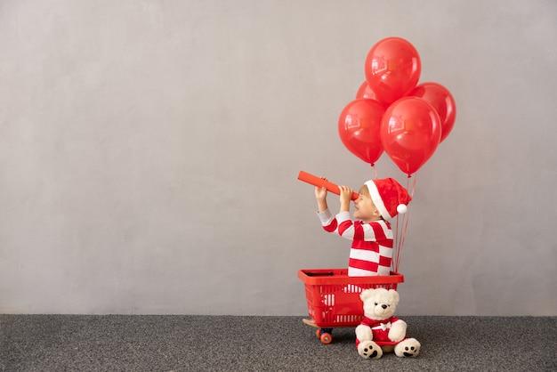 Szczęśliwe dziecko w stroju świątecznym dziecko siedzące w koszyku z czerwonymi balonami