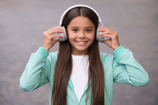Szczęśliwe dziecko w szkole słuchać muzyki lub książki audio w słuchawkach dla edukacji i radości, dzieciństwa.