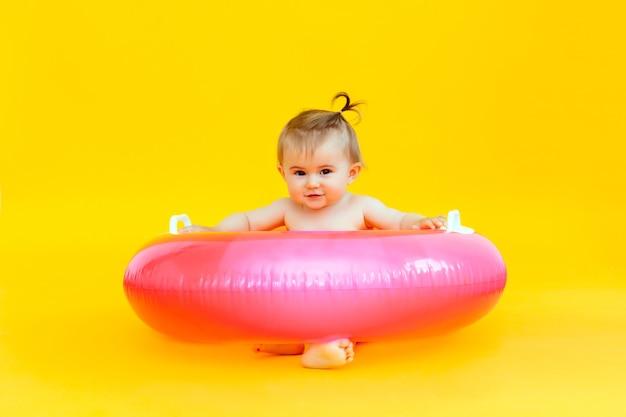 Szczęśliwe dziecko w wieku 10 miesięcy z kółkiem do pływania siedzi na żółtej powierzchni, zdjęcie studyjne dziecka w kółku do pływania