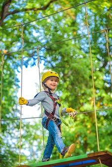 Szczęśliwe dziecko, wspinaczka na drzewa. równoważnia i mosty linowe. park linowy. dziecko wspinacza włączone